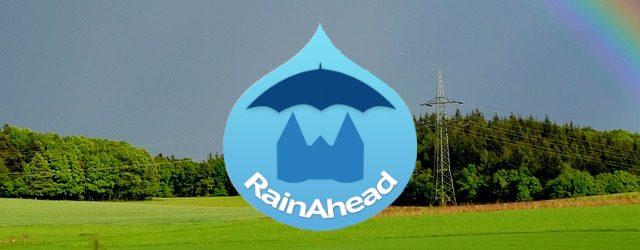Rainbow over meadow with rainahaed-logo